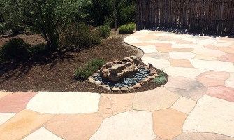 Curved flagstone patio with rock fountain