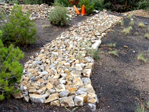 Rock media luna to collect sheet flow, slow and infiltrate it, and direct it toward a rock mulch rundown below