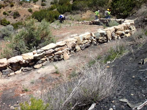 A dry stack rock wall built to divert storm drainage